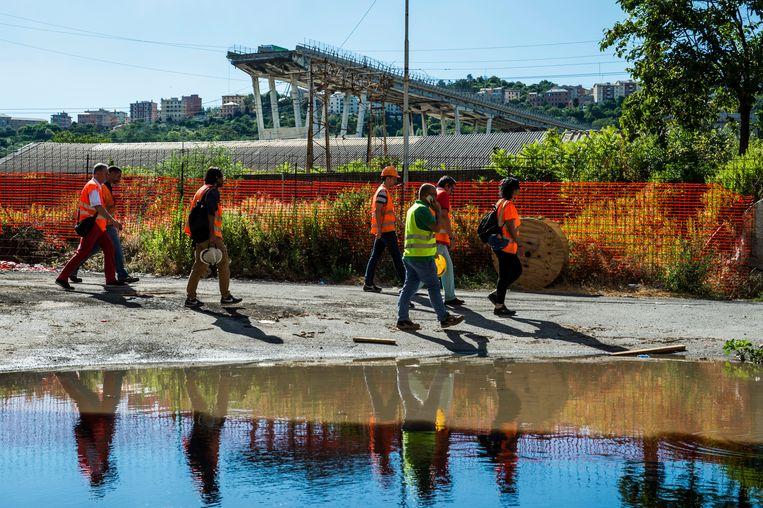 Ingenieurs en arbeiders inspecteren de omgeving van de ingestorte brug in Genua.