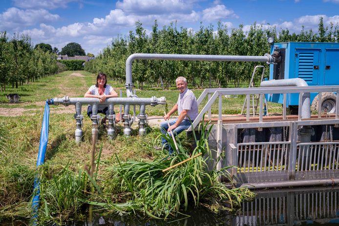 Ellen en Henk Veens bij een waterpomp van hun fruitteeltbedrijf in Slijk-Ewijk.