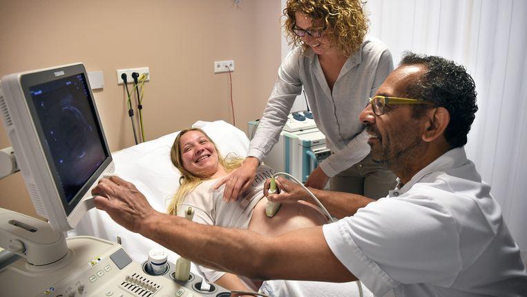 De gynaecoloog (witte jas) en de verloskundige bekijken samen met de moeder de echo in het Bravis ziekenhuis. Beeld Marcel van den Bergh