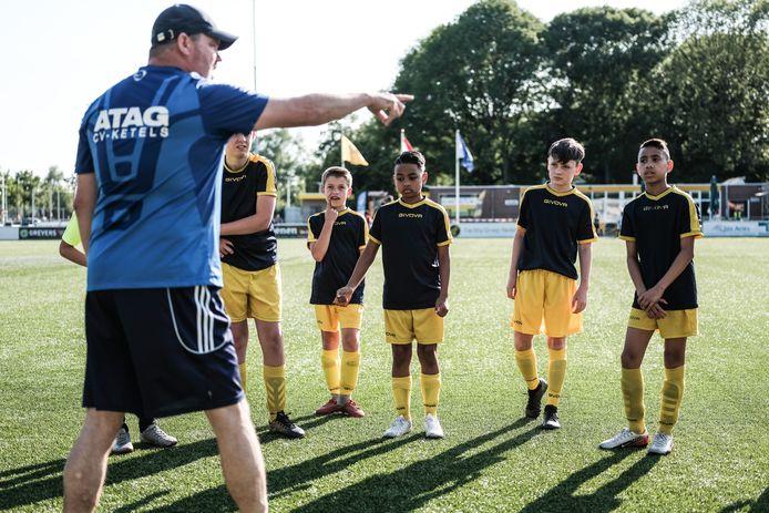 DCS-jeugdtrainer Fred Bresser doceert. Calvin, Guus, Juninho, Mees en Joshua (vlnr) luisteren aandachtig.