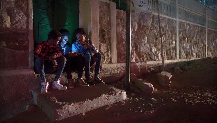Achter het muurtje bij de voetbalclub, buiten het zicht van familie, delen Somalische jongens in Hargeisha Facebookberichten van vrienden die de overtocht naar Europa hebben gemaakt. Beeld null