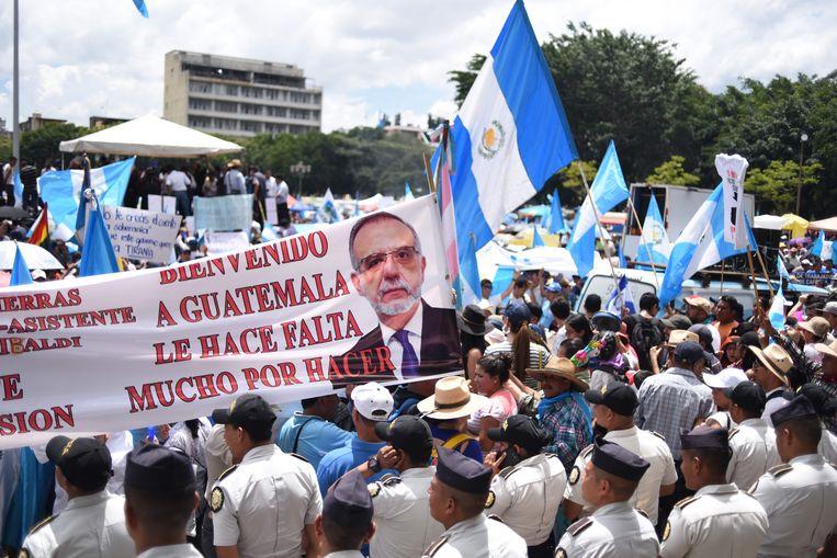 Betogers in Guatemala-Stad met een spandoek waarop het hoofd is afgebeeld van de Colombiaan Iván Velásquez, voorzitter van de Commissie tegen Corruptie en Straffeloosheid in Guatemala (Cicig), en de tekst 'Welkom in Guatemala, u bent nodig, nog veel te doen'.