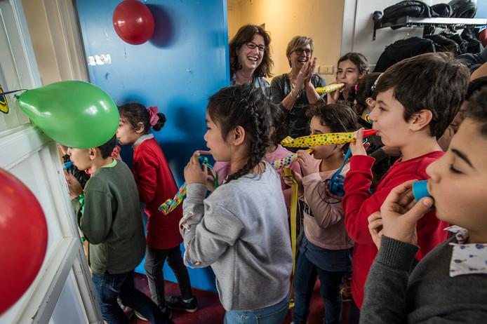 Leerlingen van IMC Weekendschool nemen voor de start van het lesprogramma feestelijk het lokaal in gebruik, nadat wethouder Miriam Haagh de lintjes met de kinderen heeft doorgeknipt.