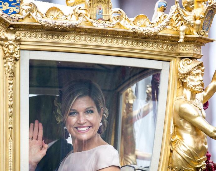 De koningin zwaait naar het publiek langs de route.