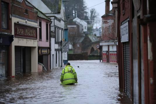 Een man waadt door de overspoelde straten van Dumfries in Schotland.