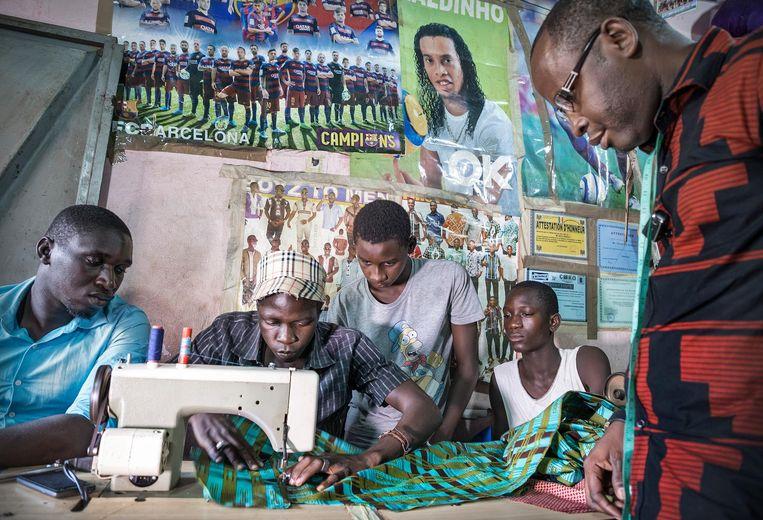 Kleermaker Ibrahim Sabaly geeft in zijn atelier in Kolda les aan zijn 5 pupillen. Hij is verkozen tot een van de 280 leermeesters in zijn regio met het doel vakmanschap over te dragen aan de werkloze jeugd. Beeld Sven Torfinn