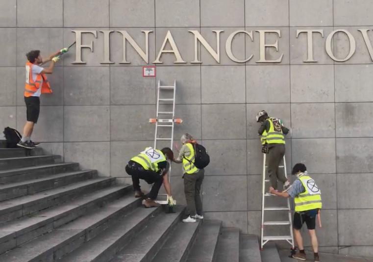 Leden van Extinction Rebellion verwijderen de letters van de Financietoren in Brussel.