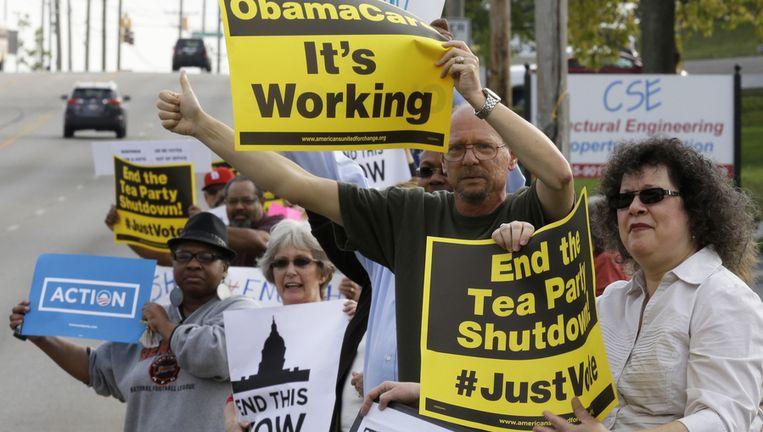 Demonstranten protesteren voor het kantoor van de Republikeinse spreker van het Huis, John Boehner. Ze willen dat de government shutdown zo snel mogelijk beëindigd wordt. Beeld ap