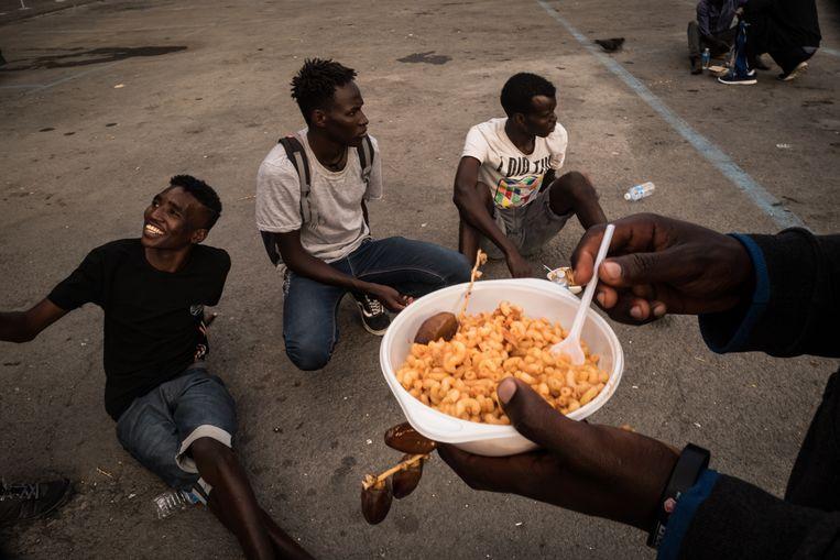 Hulporganisatie Caritas deelt voedsel uit aan migranten die onder een brug in het stadje slapen.  Beeld Nicola Zolin