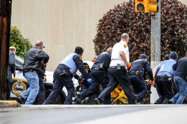 Politieagenten met een gewonde op een brancard bij de aangevallen synagoge in Pittsburgh. Beeld AP