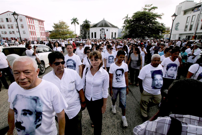 Demonstranten in Paramaribo droegen foto's van de slachtoffers van de Decembermoorden op T-shirts, tijdens een stille mars in 2012 bij de invoering van een amnestiewet.