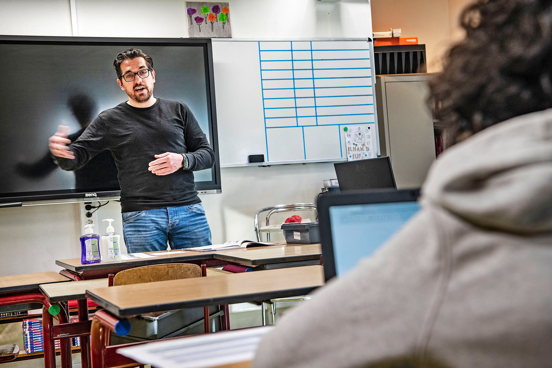 Docent Floris ter Veen praat met een leerling van basisschool De Buikslotermeer die door de coronacrisis in de problemen dreigt te komen. Beeld null