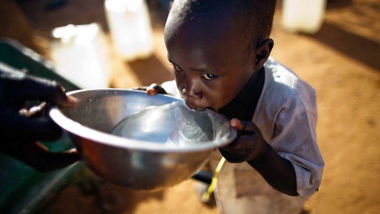 Jonge vluchteling krijgt water van hulpverlener Beeld anp