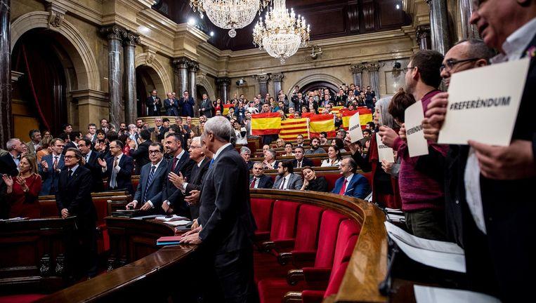 Leden van de conservatieve Partido Popular houden uit protest Spaanse en officiële Catalaanse vlaggen omhoog na de stemming in het regioparlement in Barcelona. Beeld ap
