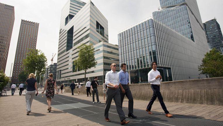 Kantoorpersoneel loopt in de zon aan de Zuidas in Amsterdam. Beeld ANP
