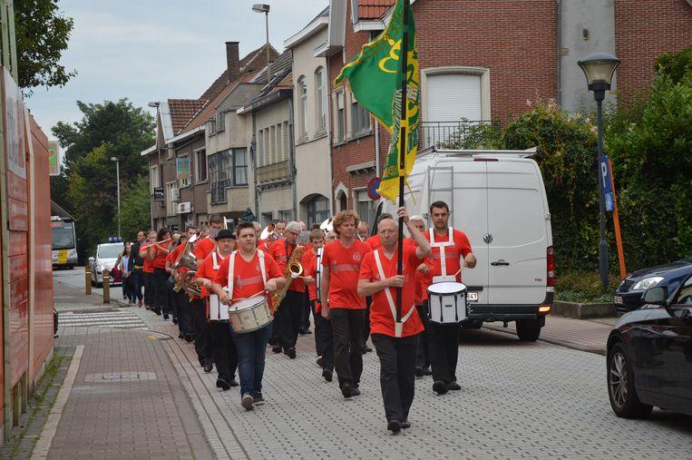 De Koninklijke Harmonie De Dendergalm tijdens een optocht naar het dorpsplein.