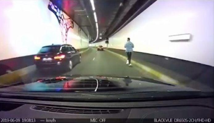 Een man rijdt op een elektrische step door de tunnel.