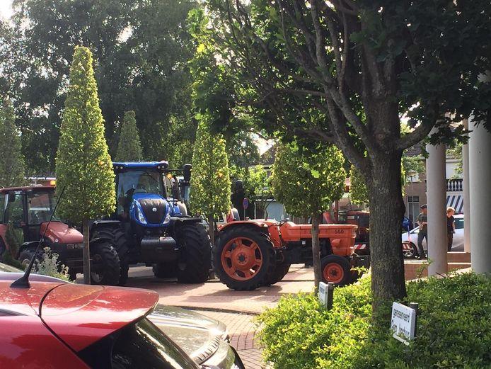 Tractors op de weg en de parkeerplaats voor het gemeentehuis.