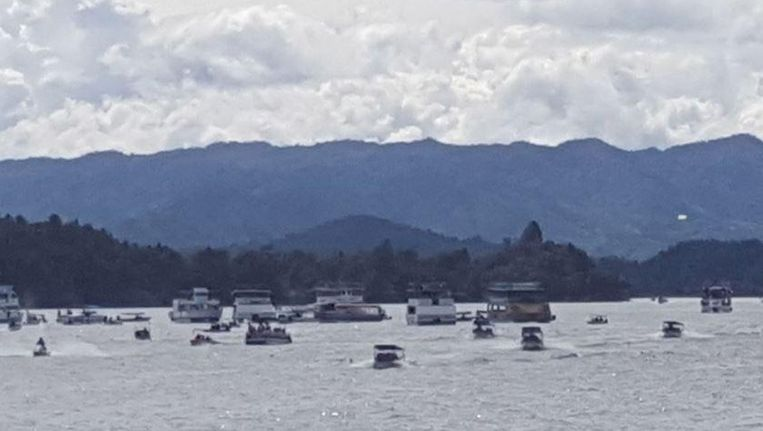 Mensen proberen met kleinere bootjes de opvarenden van de grote gezonken boot te redden.