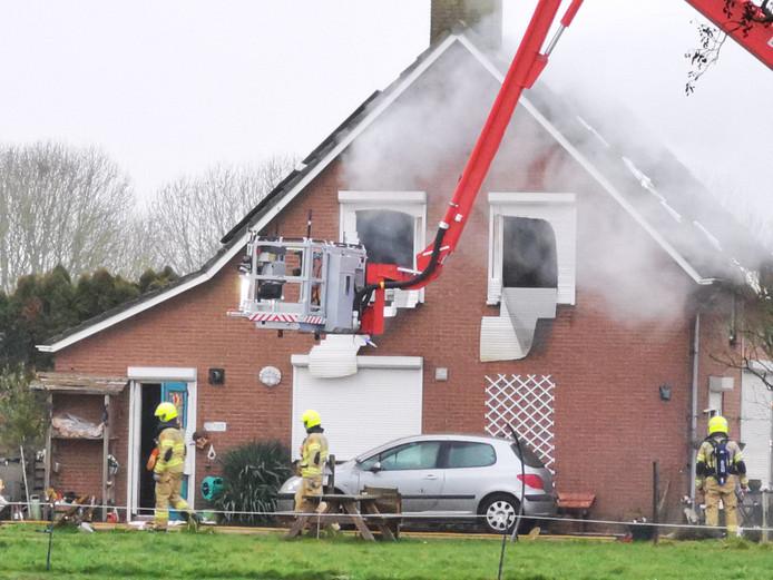 Brandweermannen na de brand bij de woning in Duiven.