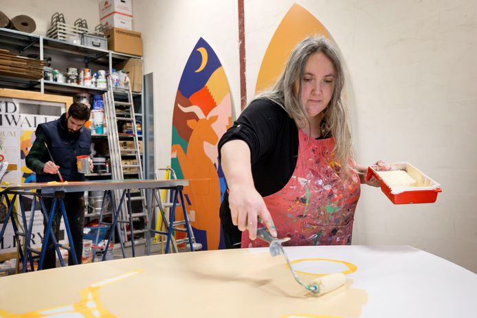 Robin Nas (links)  en Mara Piccione aan het werk aan de schilderijen die rond de grote kerk komen te staan.