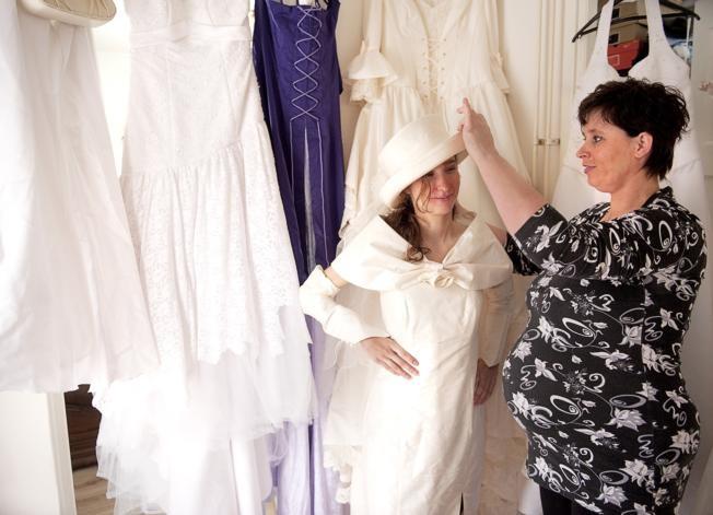 Bianca van den Berg (rechts) helpt Linda Heller bij het passen van een trouwjurk die net is binnengekomen. 'Zo kijken we even naar de maat', zegt ze. Bedoeling is dat er binnenkort een bruid in trouwt die zelf geen geld heeft voor een trouwjurk. foto Frank Poppelaars/het fotoburo