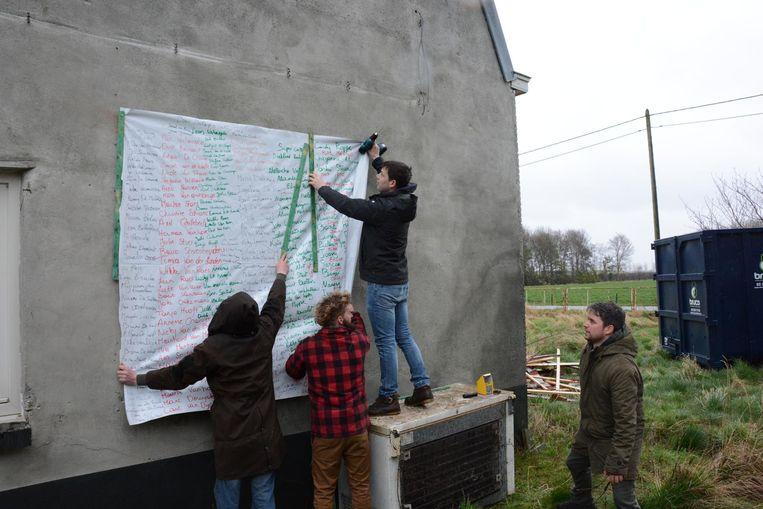 De actievoerders schreven de 400 handtekeningen over op een zeil waarmee vervolgens de bedreigde hoeve symbolisch werd ingepakt.