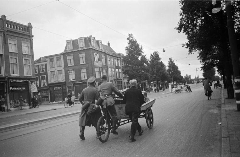 Duitse militairen vluchten met een bakfiets vol bezittingen op Dolle Dinsdag naar het station nabij de Rijnstraat in Den Haag. Beeld Hollandse Hoogte / Nederlands Fotomuseum