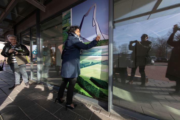 Februari 2019: wethouder Irene Korting beplakt de pui van een leegstaande winkel in Swifterbant om het aangezicht aantrekkelijker te maken.