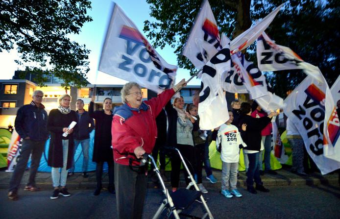 De protestvlaggen wapperen bij zorgcentrum De Schutse in Lopik, met op de achtergrond de koepeltentjes waarin actievoerders net zo lang blijven slapen, tot er meer personeel in de nachtelijke uren komt.