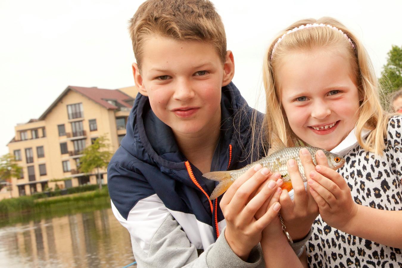 Tijmen Meijer (10) helpt Rosalie van Sambeek (6) met haar voorn