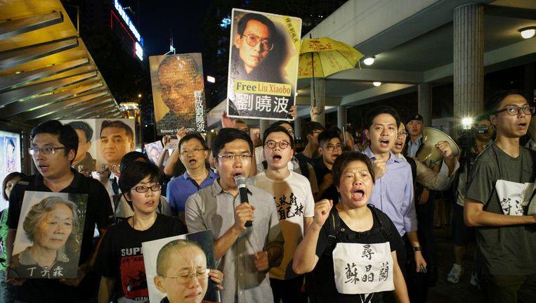 Pro-democratie protestanten met foto's van Liu Xiaobo, Hong Kong 2017. Beeld AFP