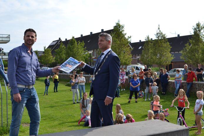 Bewoner Peter de Jong overhandigt burgemeester Dirk Heijkoop van Hardinxveld-Giessendam een petitie met ruim 500 handtekeningen tegen de mogelijke verhuizing van korfbalvereniging Vriendenschaar.