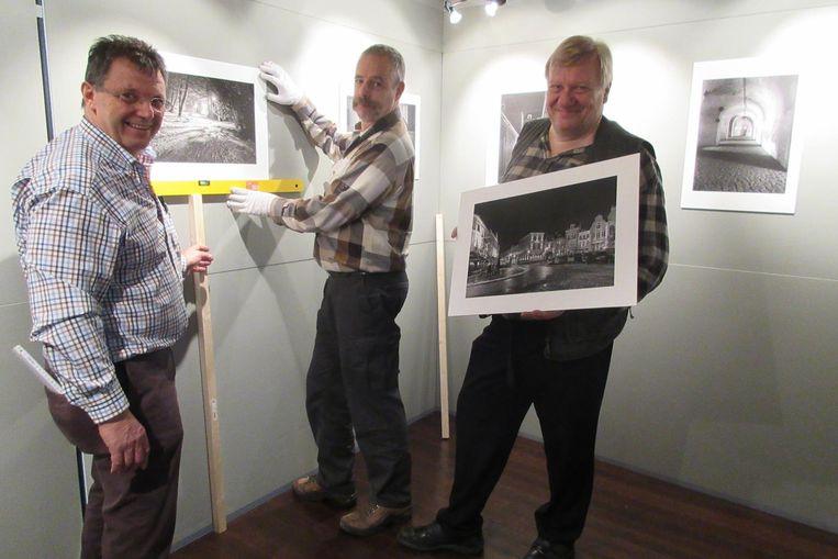 Martin Verheyden (rechts) hangt samen met enkele leden de foto's op voor de expo.