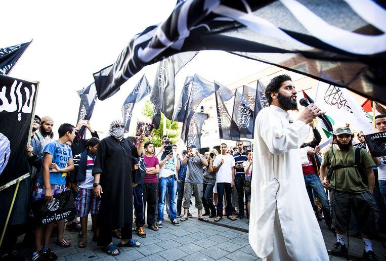 De van ronselen voor de jihad verdachte Azzedine C. (L) spreekt tijdens een pro IS-demonstratie in de Haagse Schilderswijk, juli vorig jaar. Beeld ANP