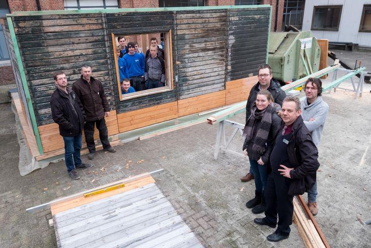 De delegatie van het Fort en leerlingen van PTS bij de noodwoning die wordt opgebouwd.
