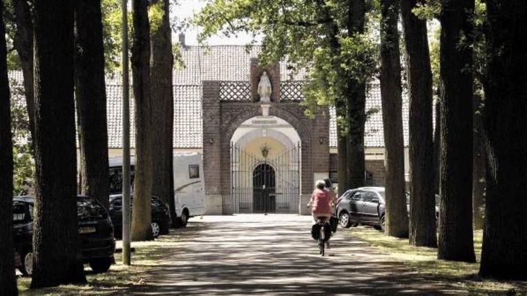 De ingang van de Achelse Kluis (boven) ligt in Nederland; de rest in Vlaanderen. Links: de Achelse producten uit de abdijwinkel. (FOTO'S JEROEN THIJSSEN) Beeld