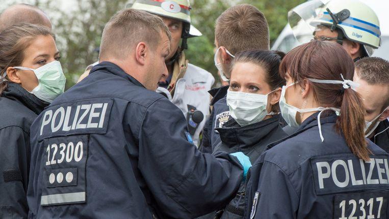 Duitse politie buiten het ziekenhuis in Berlijn is voorzien van mondkapjes om ze te beschermen tegen een mogelijk geval van ebola. Het lijkt erop dat het vals alarm is geweest. Beeld ap