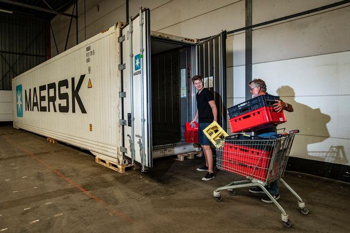 Vrijwilligers Joost Norel en Martin Elshof (rechts) van de voedselbank zetten de eerste kratten in de zeecontainer in de nieuwe hal van de voedselbank.