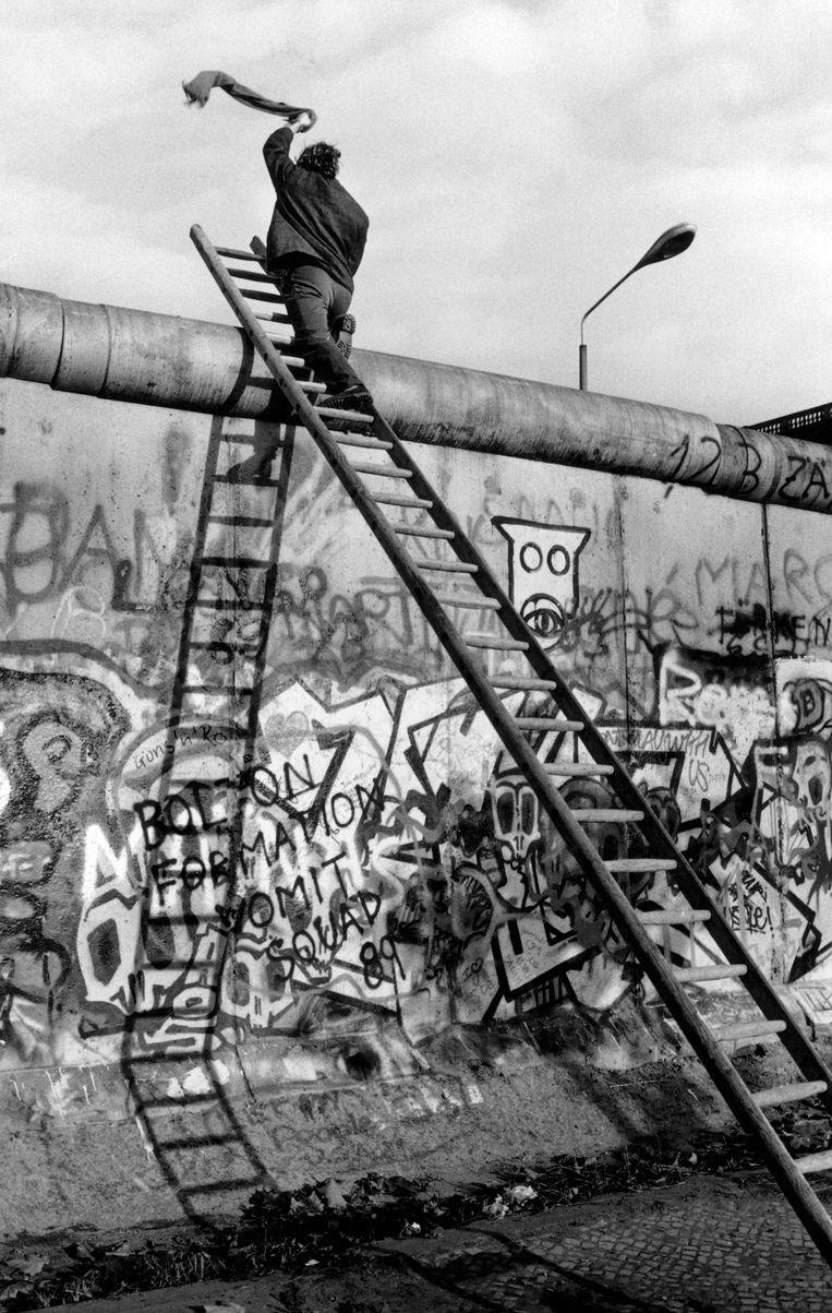 Berlijn, november 1989. n. Man klimt met een ladder de muur op.  Beeld Jirina Simajchlova/Hollandse Hoogte