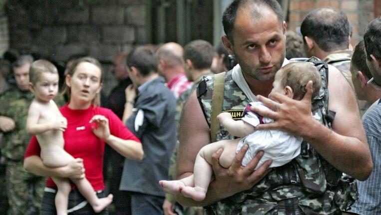 Een soldaat redt een baby uit de bezette school in Beslan, september 2004. Bij de terreuractie komen uiteindelijk honderden mensen, voornamelijk kinderen om het leven. Beeld ANP