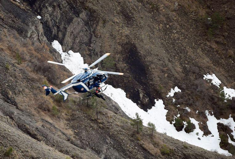 Een helikopter brengt onderzoekers naar de crashsite van het Germanwings-toestel. Beeld AFP