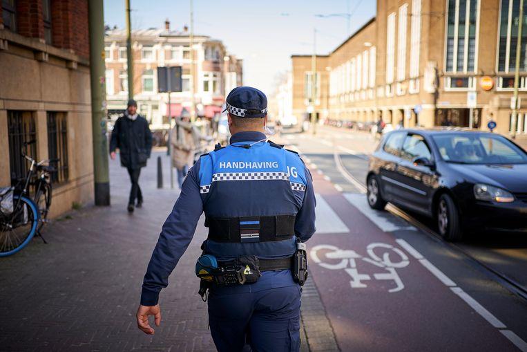 Een boa van de gemeente surveilleert in het centrum van Den Haag. Beeld Phil Nijhuis