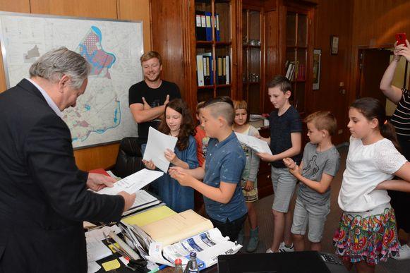 De scholieren overhandigen een bundel wensen aan de burgemeester Marc Van de Vijver.