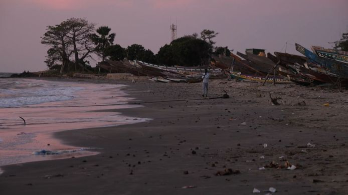 This image grab taken from an AFP video shows a man walking on a beach, in Barra on December 5, 2019, after at least 62 people migrants died on December 4, 2019 when their makeshift vessel capsized off the coast of Mauritania, including 52 migrants from Gambia. (Photo by Romain CHANSON / AFPTV / AFP)