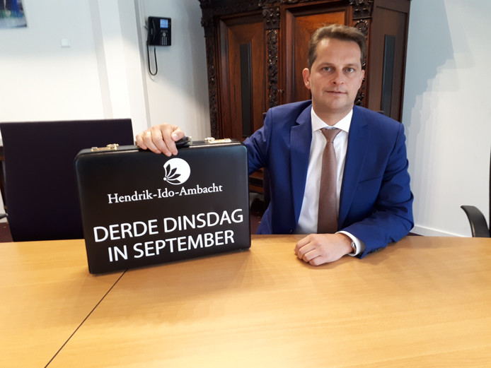 Wethouder André Flach met zijn koffertje.