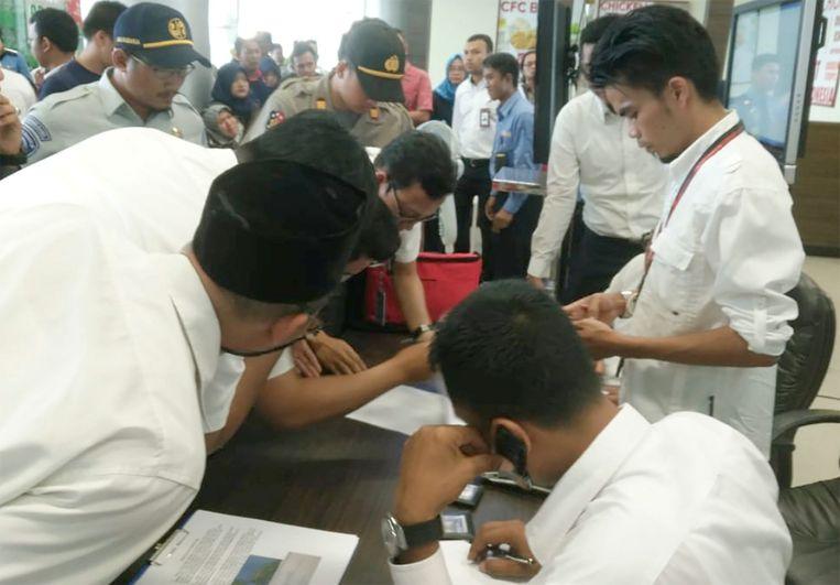 Grondpersoneel van Lion Air bekijkt de passagierslijst van de gecrasthe vlucht JT610.