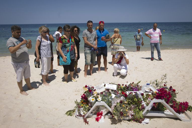 Toeristen en Tunesiërs rouwen bij de bloemen op de plek van de aanslag in Sousse. Beeld anp