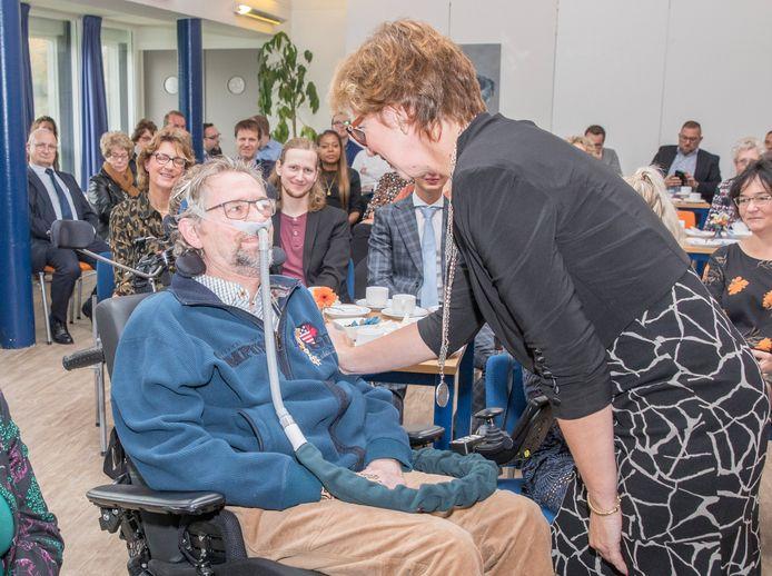 Klaas van der Meulen wordt gefeliciteerd door burgemeester Margo Mulder na het opspelden van de Koninklijke onderscheiding.