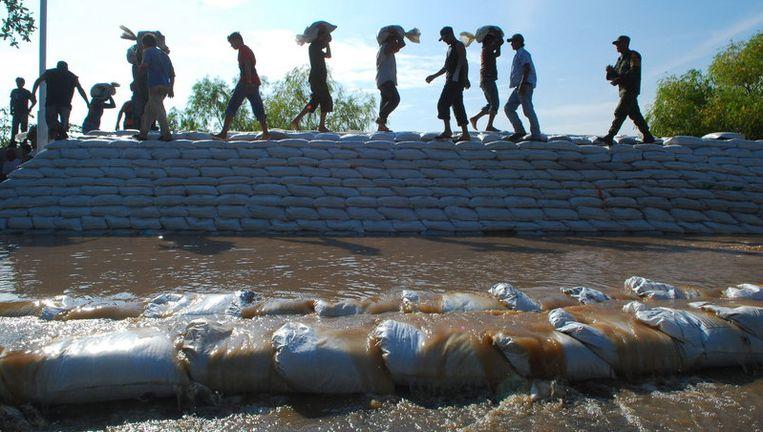 Militairen en bewoners bouwen met zandzakken een dam bij de Grijalva-rivier. Foto EPA Beeld